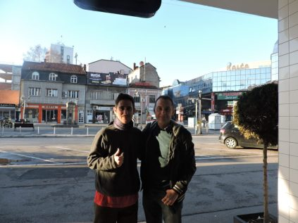 Junto a Bratislav, afuera del café y mirando hacia otro lado