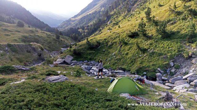 Tienda de acampada junto a un arroyo en medio de la montaña
