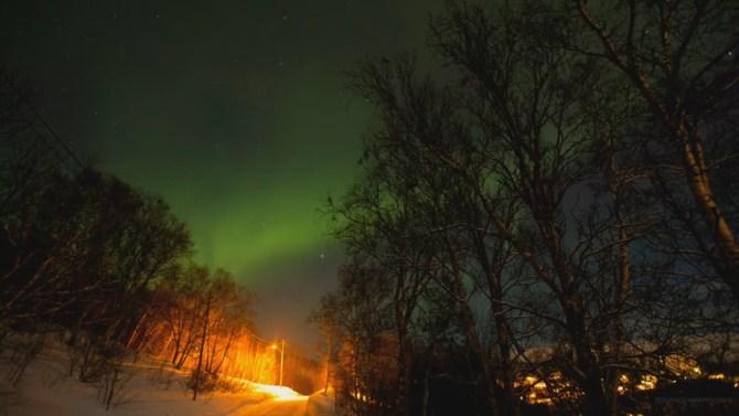 Cielo nocturno con aurora boreal verde