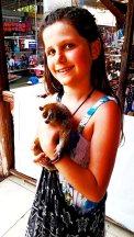 Niña sonriente sujetando animal exótico mercado flotante Damnoen Saduak