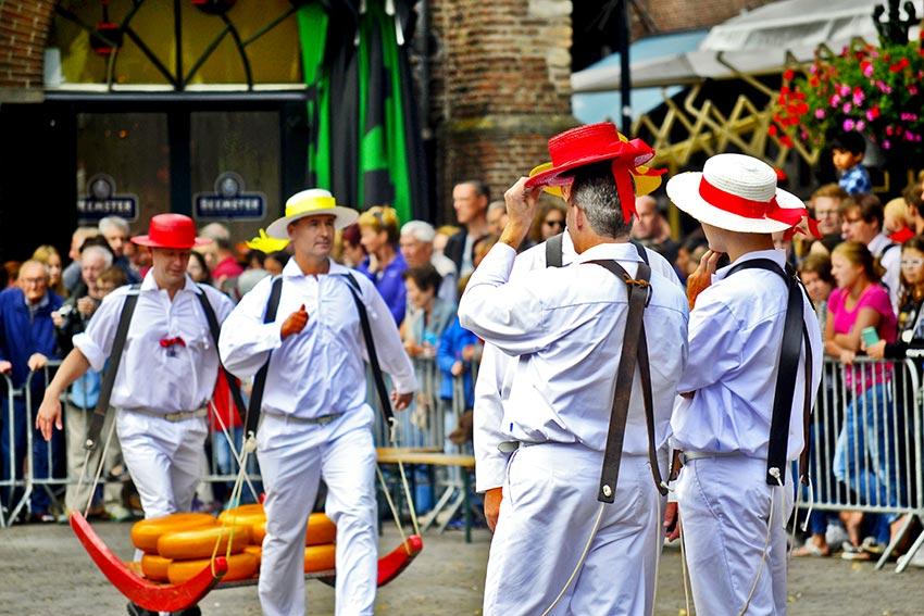 Mozos blanco tirantes portando queso Plaza Mercado Alkmaar