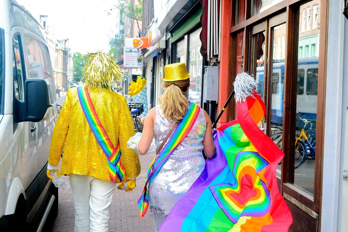 Turistas espaldas disfraces color Desfile Orgullo Gay Amsterdam