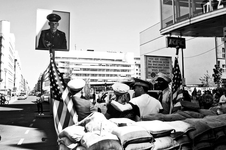 Turistas soldados espaldas Checkpoint-Charlie Berlín Alemania