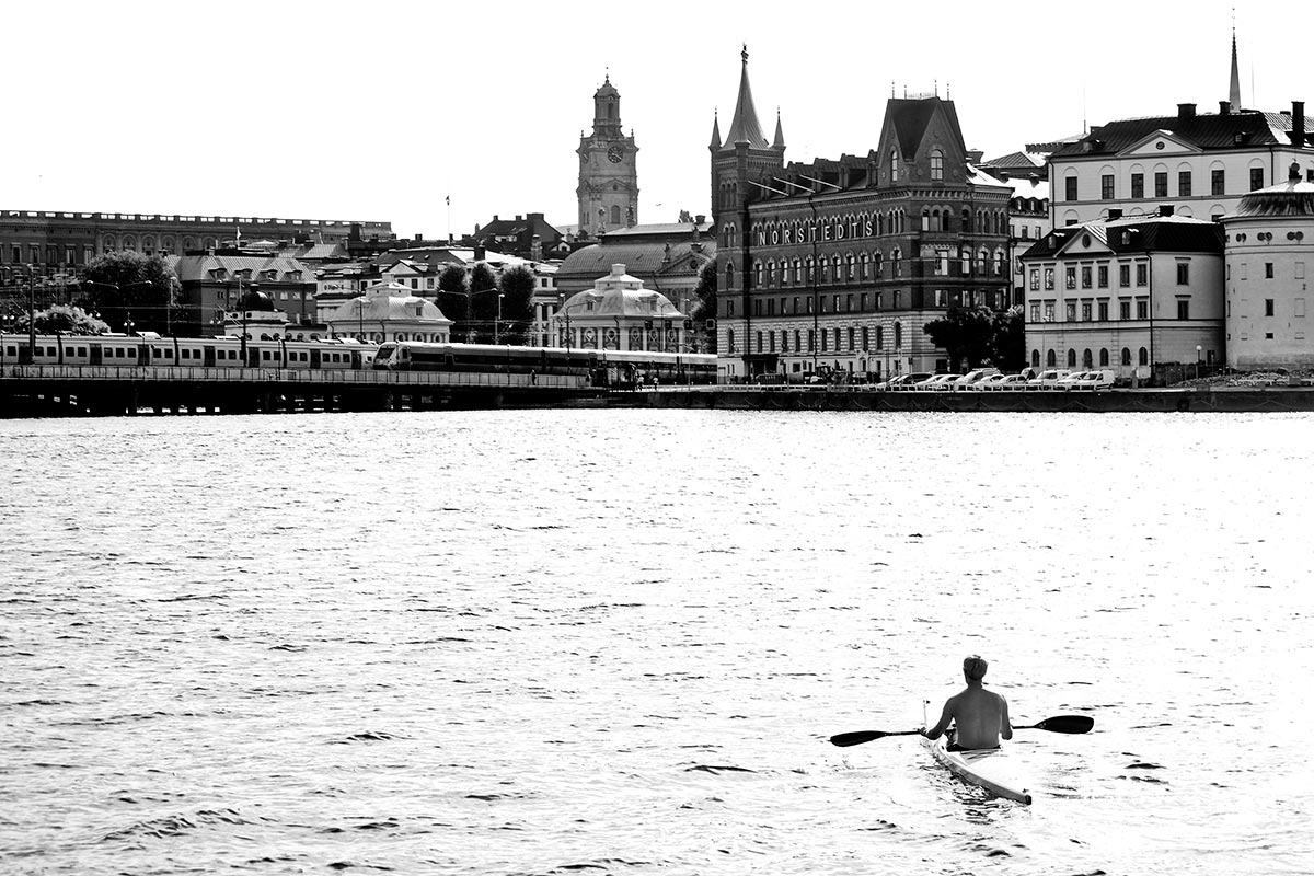 Hombre piragua archipiélago Riddarfjärden panorámica Södermalm Estocolmo Suecia blanco y negro