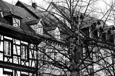 Escultura Jesucristo camuflado ramas árboles fachadas viviendas centro histórico Offenburg Alemania
