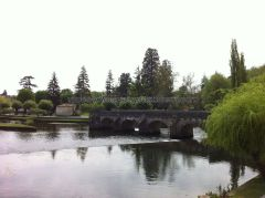 represas del canal para los paseos en barca de los turistas; es broma, eran para el molino; puente peatonal a la derecha, y arboleda y campa al fondo