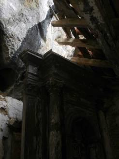 Detalle de la parte de arriba del altar de madera, con el tejado roto
