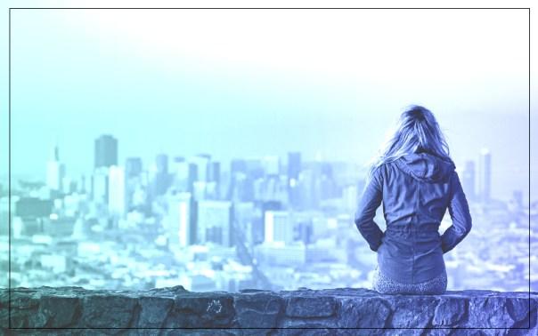 menina sentada no parapeito de um prédio, com um caso e as mãos no bolso. ao fundo, a paisagem de uma cidade cheia de prédios