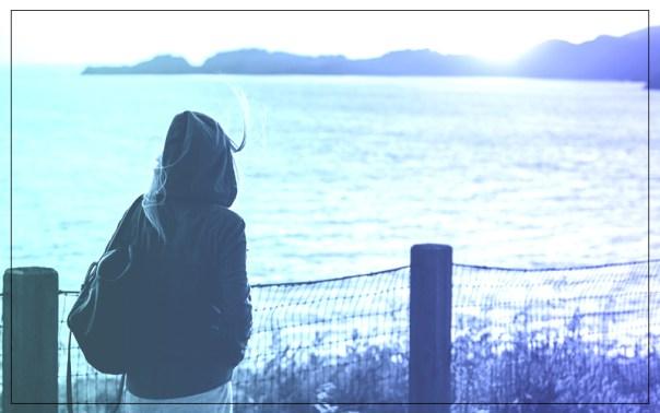 imagem de uma menina usando capuz, com os cabelos balançando pelo vento olhando para o horizonte, onde é possível ver o mar e montanhas
