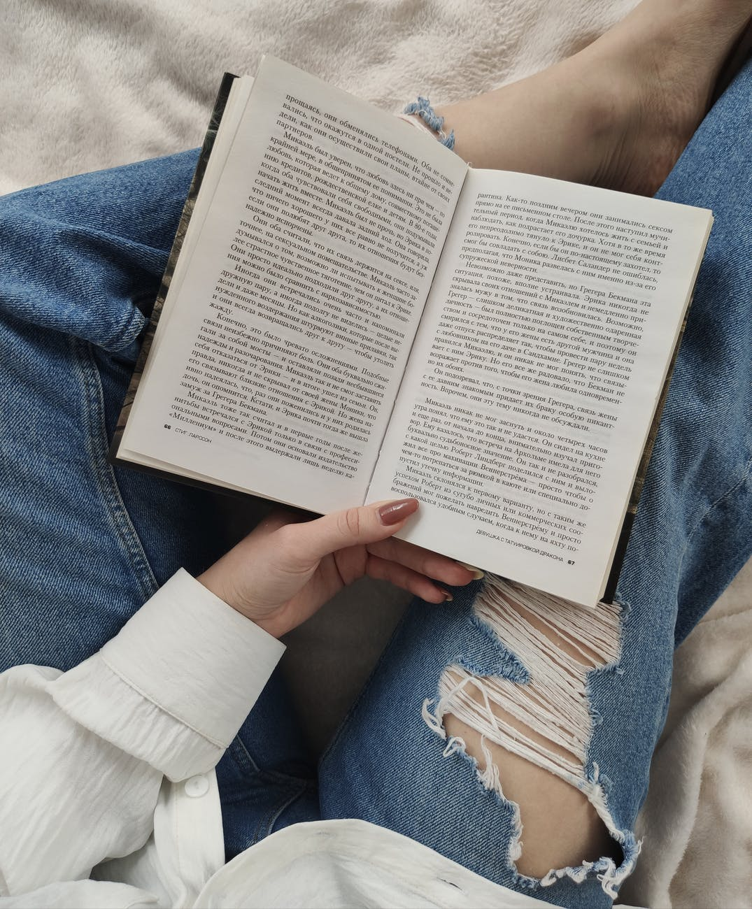 crop faceless woman reading book on bed
