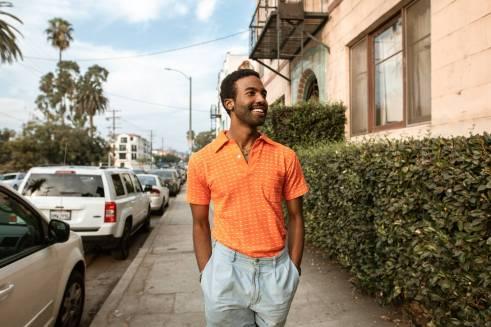 smiling man walking on a sidewalk