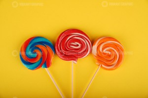 Assorted round lollipops on yellow background