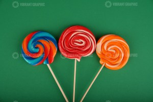 Colorful lollipop isolated on green background
