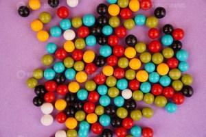 Delicious round dragee candies on purple background