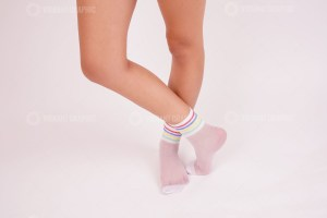 Female legs in white socks in the studio