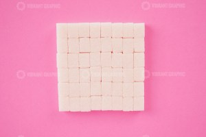 Stack of cube sugar on pink background
