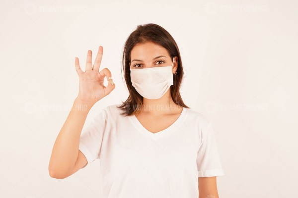 Girl in medical mask showing OK gesture