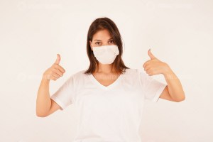 Girl in medical mask showing shows thumb up