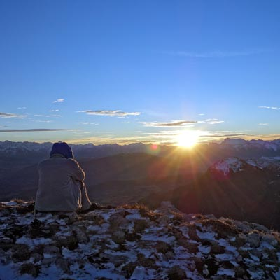 Photo of person contemplating sunset over mountains