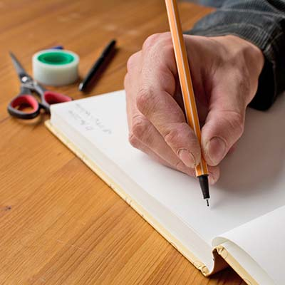 Man writing with pen in notebook