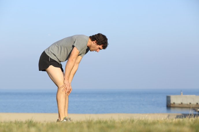 Exhausted runner man resting on the beach after workout