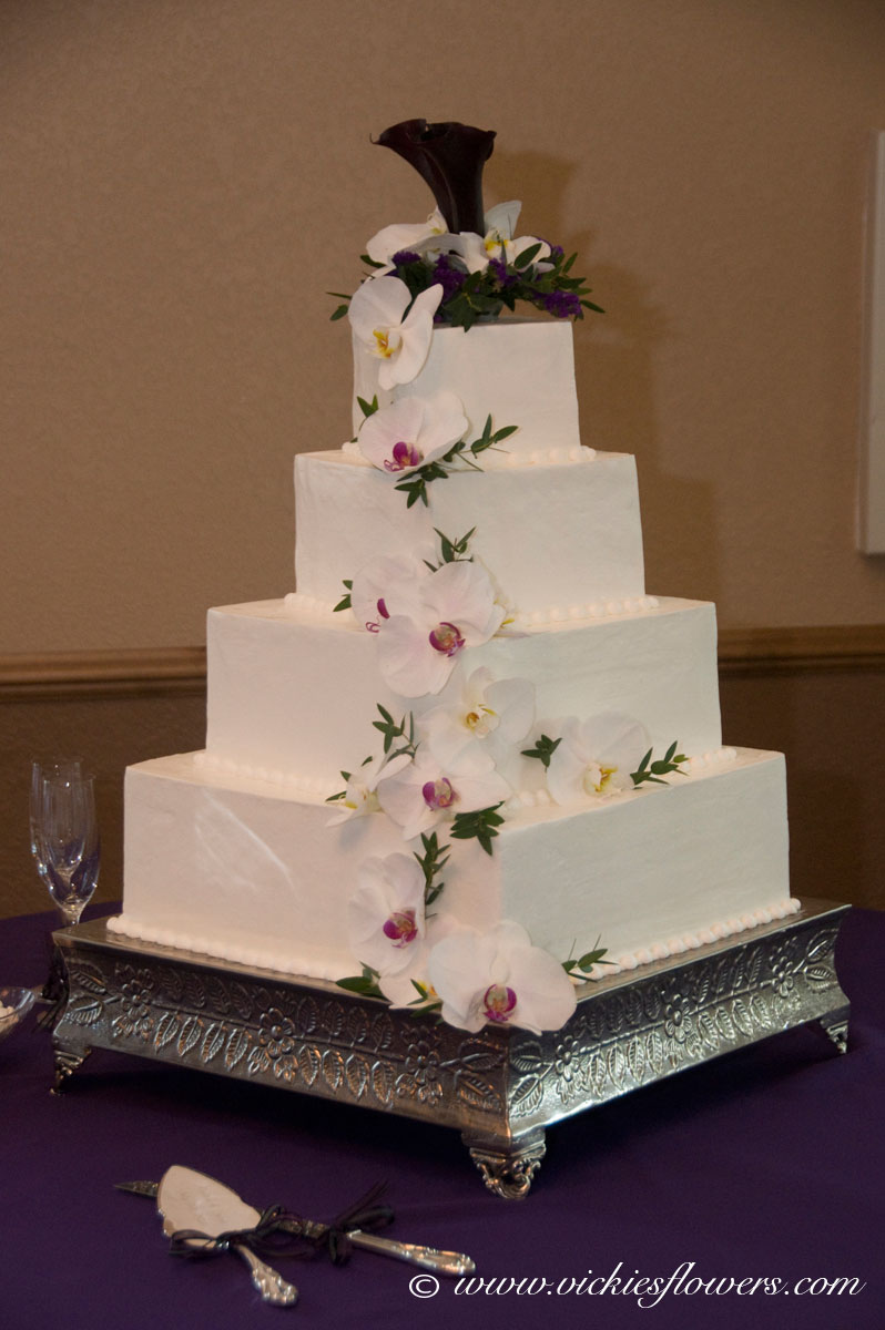 Wedding Cake Toppers   Vickie s Flowers  Brighton Co Florist Wedding Cake Toppers 007   Cascading white Orchids on a 4 tier wedding cake  with a dark purple Calla Lily and white Phalaenopsis
