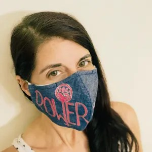 This image is a white woman with dark brown long hair wearing a face mask. The mask is made of denim and painted with a design stating Power not Pity. The last line of the letter W in Power has the woman symbol wit the fist coming up from the last line of the W and the inverted t or plus sign + coming down from the last line of the W.