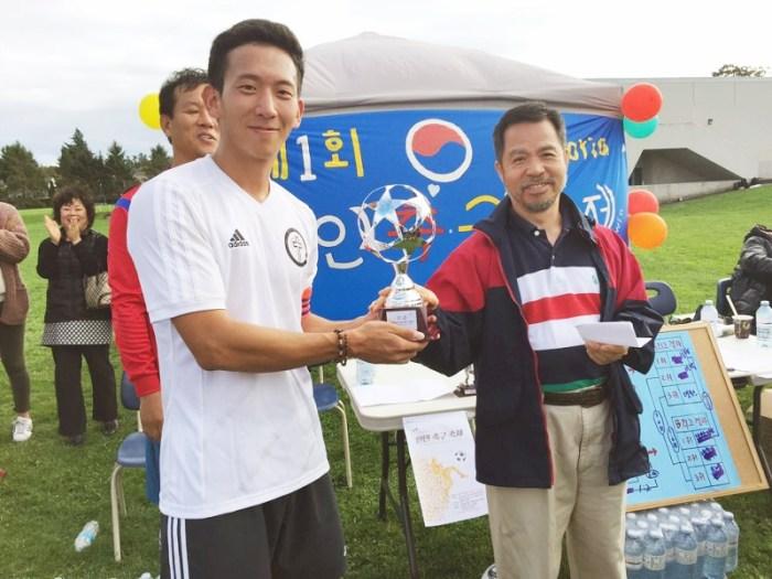 대회장인 김헌웅 한인회 부회장으로 우승 트로피를 받고 있는 성당팀의 변용수 선수 .