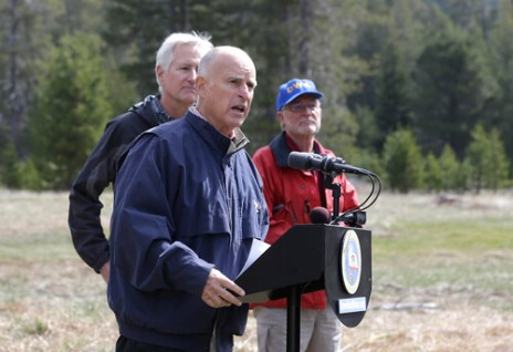 Gov. Jerry Brown, center, answers a question concerning the executive order he signed requiring the state water board to implement measures in cities and towns to cut water usage by 25 percent compared with 2013 levels, at Echo Summit, Calif., Wednesday, April 1, 2015. (AP Photo/Rich Pedroncelli)