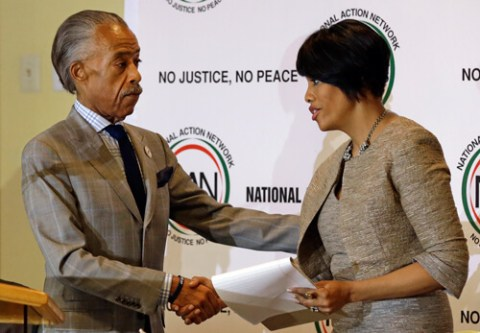 """NBC's Al Sharpton shakes hands with Baltimore Mayor Stephanie Rawlings-Blake as she prepares to speak at a summit to address issues surrounding the death of Freddie Gray and its aftermath at New Shiloh Baptist Church, Thursday, April 30, 2015, in Baltimore. Note the """"No Justice, No Peace"""" slogan behind them. (AP Photo/Patrick Semansky)"""