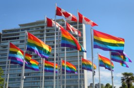 Rainbow colored Gay Pride Flags and Canadian Flags flutter in the wind in Vancouver. British Columbia, Canada.