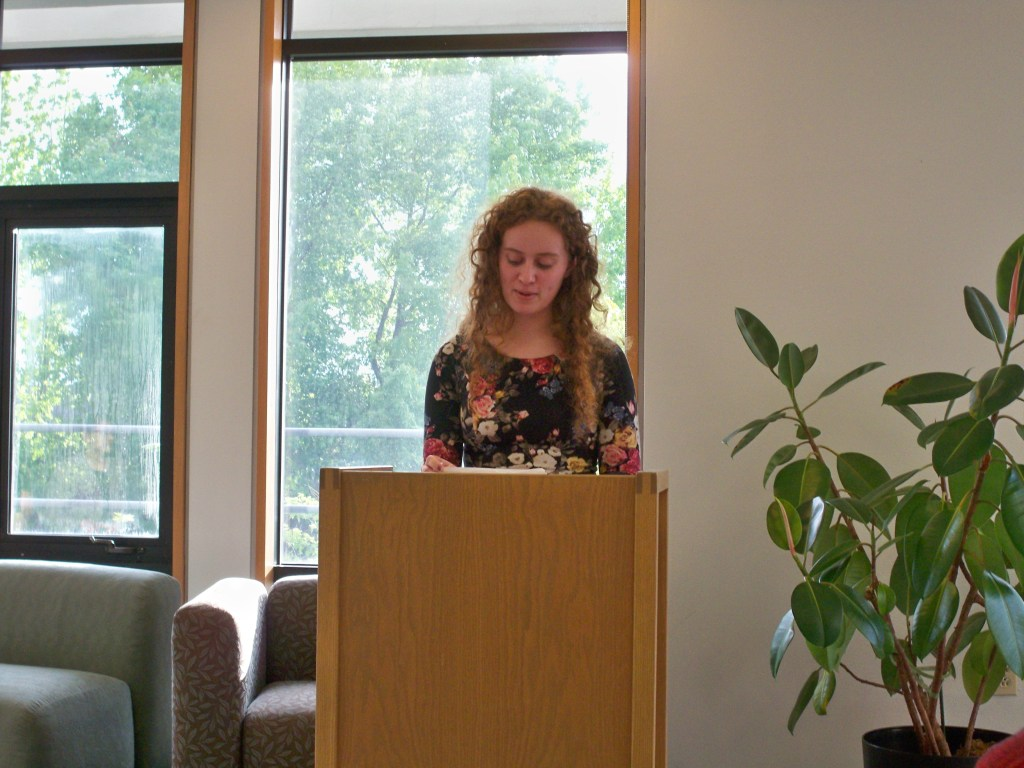 image of victoria reading her short story from behind a pulpit