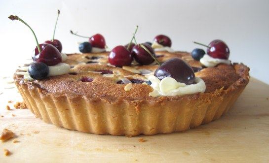 side view of cherry blueberry frangipane tart with almond buttercream