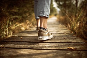 Photo: persons feet in running shoes walking down boardwalk