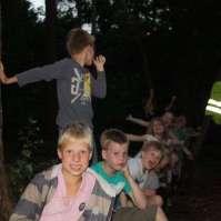 De jongere kinderen spelen een eigen spel in het donkere bos