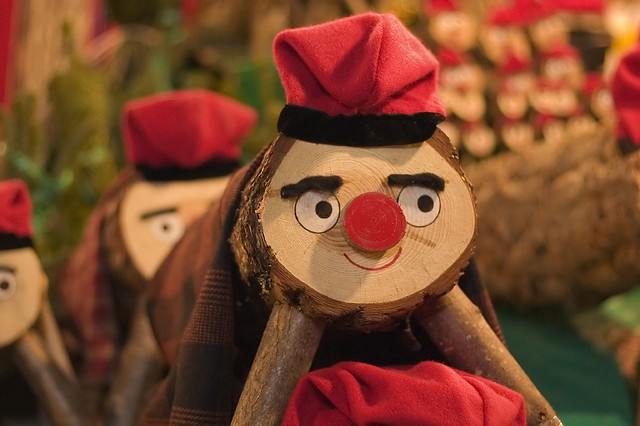 A photograph of a small log wearing a red hat. It has a painted face and thick felt eyebrows.