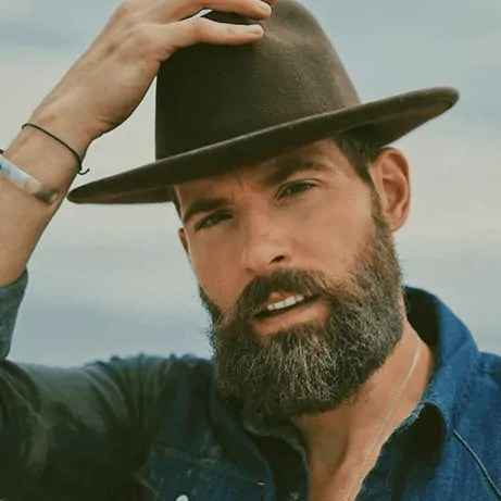 Matthew Nadu, posting with full beard and cowboy hat