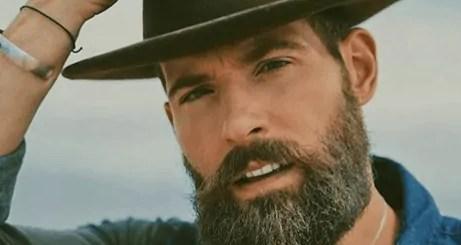 Matthew Nadu, posting with full beard and cowboy hat