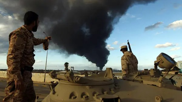 Members of the Libyan army stand on a tank as heavy black smoke rises from the Benghazi's port in the background on Dec. 23, 2014