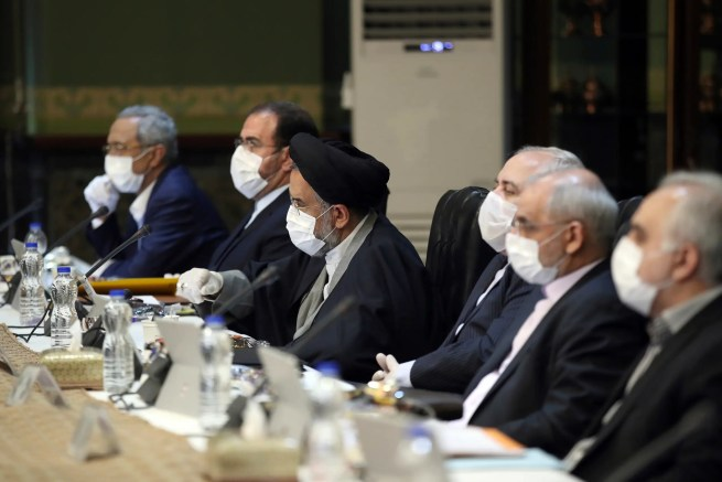 In this photo released by the official website of the Office of the Iranian Presidency, cabinet members wearing face masks and gloves attend their meeting in Tehran, Iran, Wednesday, March 18, 2020. (AP)