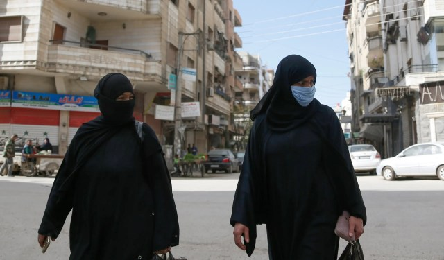 Syrian women, one of them wearing a face mask as a preventive measure against the novel coronavirus, walk along a street in the capital Damascus on April 1, 2020. (AP)