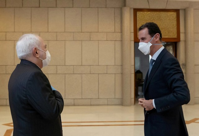 Syria's President Bashar al-Assad and Iran's Foreign Minister Mohammad Javad Zarif, wearing face masks as protection against the spread of the coronavirus disease (COVID-19), meet in Damascus, Syria, in this handout released by SANA on April 20, 2020.