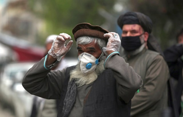 Daily-wage workers wear a protective face mask to help curb the spread of the coronavirus in Kabul, Afghanistan, April 20, 2020. (AP)