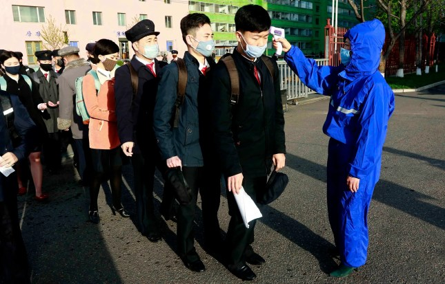 Students wearing facemasks have their temperature checked as a precaution against a new coronavirus as their university reopened following vacation, at Kim Chaek University of Technology in Pyongyang on April 22, 2020. (AP)
