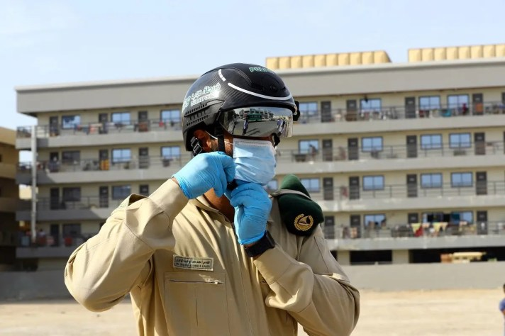 A police officer wears a smart helmet as he uses it to test the temperature of the workers during the outbreak of the coronavirus disease (COVID-19) in Dubai. (Reuters)