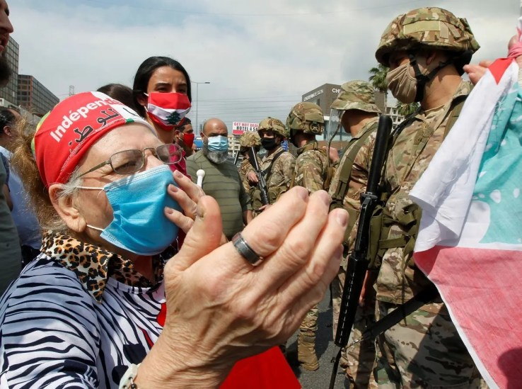 An elderly woman wearing a face mask gestures during a protest against the collapsing Lebanese pound currency and the price hikes, in Zouk, north of Beirut, Lebanon April 27, 2020. (Reuters)