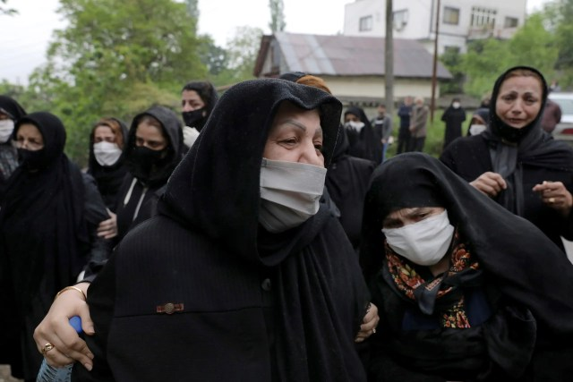 Relatives of a victim who died from the new coronavirus, mourn at the gate of a cemetery in the city of Ghaemshahr, in north of Iran on April 29, 2020. (AP)
