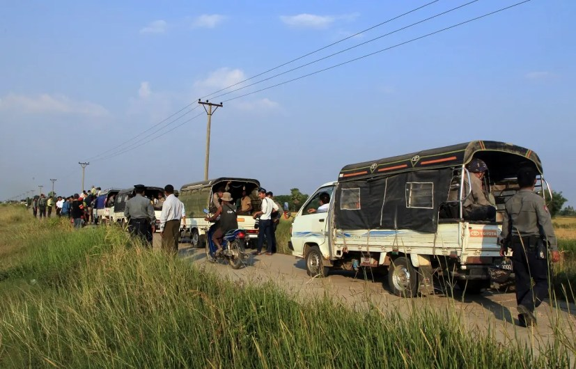 A convoy of trucks carrying detained Rohingya Muslims who fled by boat from Rakhine State are seen while police provide security in KyaukTan township, about 100 kilometers from Yangon, Myanmar. (File photo: AP)