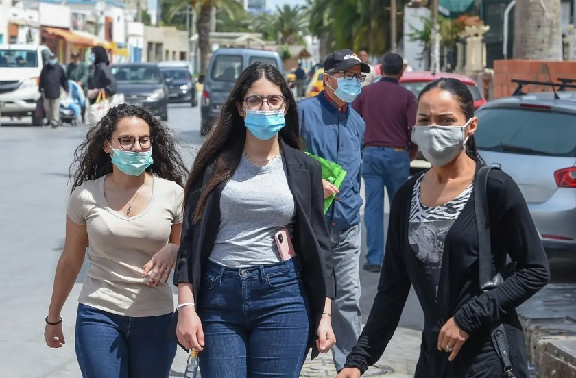 Tunisians wearing protective masks amid the COVID-19 pandemic walk by on a street in the Kram area of the capital Tunis on May 8, 2020. (AFP)