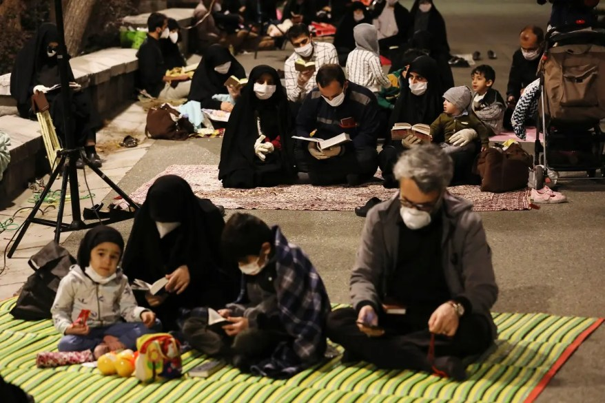 Worshippers wearing protective face masks pray outside the mosque of the Tehran University in Laylat al-Qadr, during the holy fasting month of Ramadan, Iran, May 12, 2020. (AP)